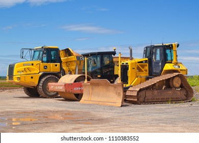 TRURO, CANADA - JUNE 10, 2018: Caterpillar bulldozer, Dynapac roller and John Deere dump truck parked outside on a sunny day.