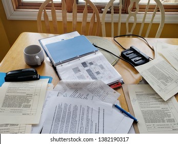 TRURO, NOVA SCOTIA/CANADA-MARCH, 2019: A kitchen table with teacher's papers, essays, binders, stapler, charger, coffee mug and rubrics scattered on it so teacher can work at home after school.