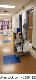 TRURO, NOVA SCOTIA/CANADA-MAY 3, 2019: A janitor's cart with supplies sits outside a room along an empty hallway to be used for end of the day cleaning.