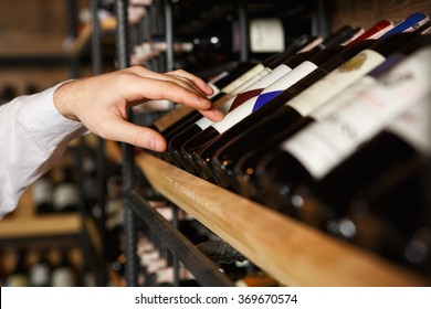 Trust him with the choice. Closeup shot of a sommelier choosing a wine bottle from the shelf in a wine cellar
