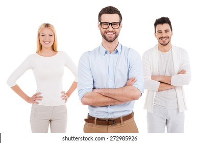 Trust to professionals. Three confident young people in smart casual wear looking at camera and smiling while standing against white background
