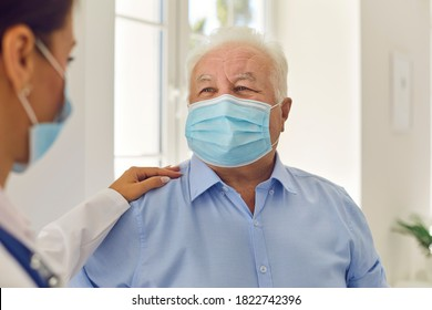 Trust and support. Happy senior patient and doctor, wearing medical face masks, communicating in hospital office. General practitioner in modern clinic patting aged man on the shoulder cheering him up