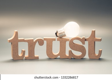 TRUST wood word with glowing light bulb, trust for success business concept