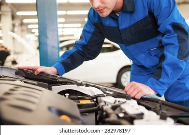 Trust your car to the experts. Close-up of concentrated young man in uniform examining car while standing in workshop