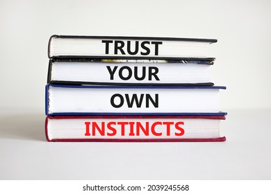 Trust your own instincts symbol. Books with words 'Trust your own instincts'. Beautiful white background. Businessman hand. Copy space. Business and trust your own instincts concept.