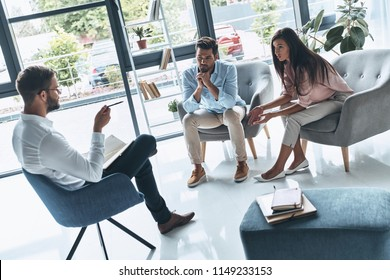 Trust your therapist. Young married couple talking while sitting on the therapy session with psychologist