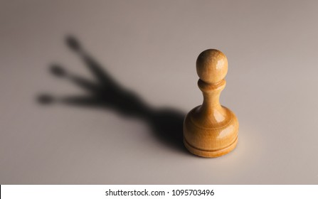 Trust yourself, self confidence concept. Wooden chess pawn with king shadow on gray background, motivation poster