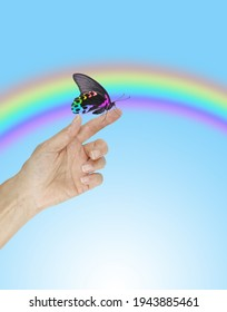Trusting Rainbow Butterfly Message Background - beautiful rainbow coloured butterfly sitting on a human finger against a wide blue sky with a massive arcing rainbow and space for copy