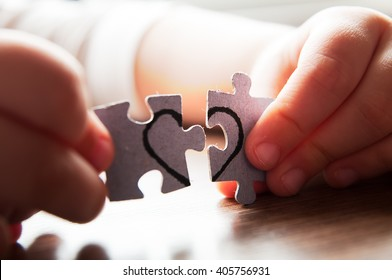 Try again or stop all - you decide, assemble puzzle. matching interlocking puzzle pieces conceptual of teamwork and problem solving, closeup of their hands