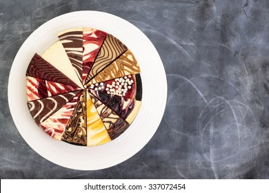 A try of fourteen different types of cheese cake on a platter from above.