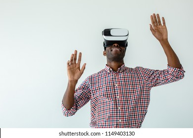 Try it. Cheerful delighted afro american man smiling and testing vr glasses against white background