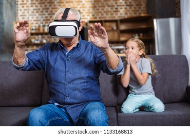 Try it on. Nice aged man wearing vr glasses while sitting on the couch with his granddaughter