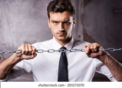 Trying to break a chain. Concentrated young man in shirt and tie trying to break a chain while looking at camera