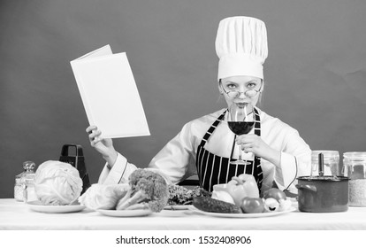 Trying a healthy dinner recipe. Pretty woman reading recipe book in kitchen. Housewife looking for cooking recipe in cookbook. Professional cook cooking vegetarian dinner according to recipe.