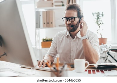 Trying to help someone. Handsome young man in eyeglasses typing something and touching headset with his hand while sitting on working place in creative office