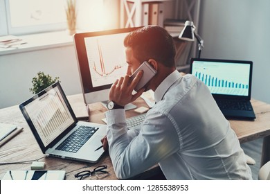 Trying to help someone. Young businessman in formalwear talking on the phone and analyzing data using computer while sitting in the office
