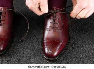 Trying new shoes. Man is putting on a new pair of luxury burgundy full grain leather shoes at footwear store