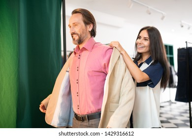 Trying on clothes. Handsome attractive smiling cheerful nice-looking man trying on a new beige blazer in the store while good-looking beautiful woman helping him.