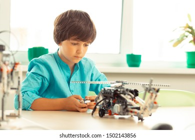 Trying to set in motion. Concentrated elementary schoolboy sitting in the classroom with remote control in his hands turning on a helicopter model.