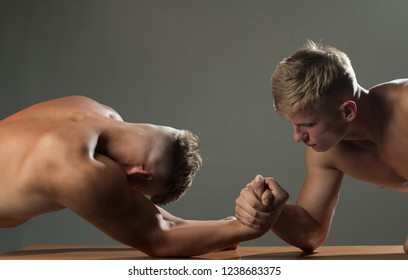 Trying strength. Twins competitors arm wrestling. Men competitors try to win victory or revenge. Twins men competing till victory. Strength skills. Revenge in sport.