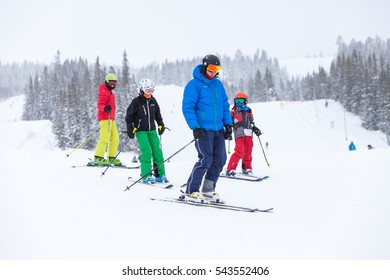 TRYSIL, NORWAY, FEBRUARY 2015, father with three children at the bottom of the ski slopes on a cold and overcast winter day.