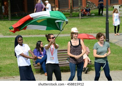 TRZEBNICA, POLAND - JULY 25: World Youth Day, pilgrims cheering with Italian and Brazilian flag in front of St. Jadwiga Sanctuary on 25th July 2016 in Trzebnica.