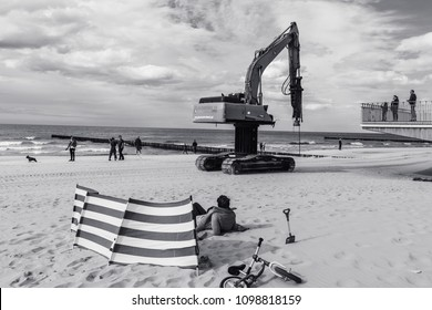 TRZESACZ, POLAND - MAY 1; 2018: The excavator for driving piles goes through the beach with tourists by the Baltic Sea.