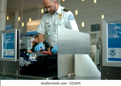 A TSA agent searches luggage at an airport. (12MP camera, NO model release, editorial only)