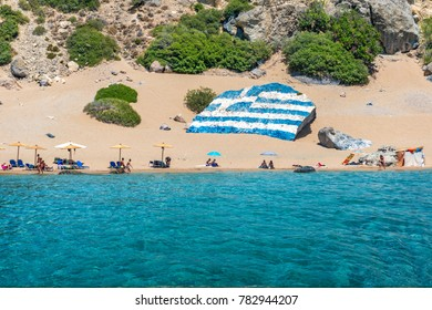 Tsambika beach with golden sand with big Greek flag painted on rock (RHODES, GREECE)