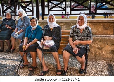 TSAMBIKA, RHODES ISLAND, GREECE – SEPTEMBER 6 2017:  Old Greek unknown women sit on the bench and enjoy afternoon near Tsambika monastery
