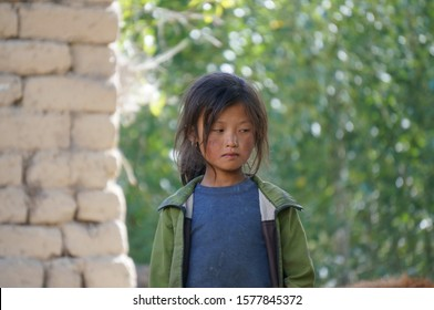 Tsarang, Upper Mustang / Nepal - August 23, 2014: A sad little girl of Tibetan nationality with a sunburn on her face is standing on the street.