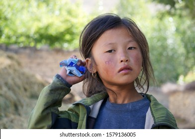 Tsarang, Upper Mustang / Nepal - August 23, 2014: Portrait of a sad little girl of Tibetan nationality with a sunburn on her face.