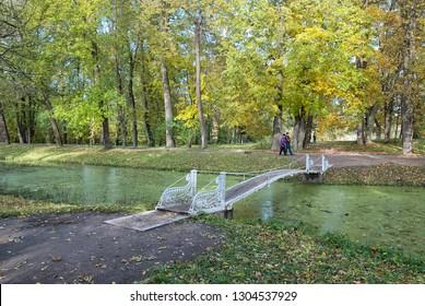 TSARSKOYE SELO, SAINT-PETERSBURG, RUSSIA – OCTOBER 8, 2018: People walk in The Alexander Park near Shaking (Hanging) Bridge over Krestovy Canal. Tsarskoye Selo is the state museum preserve