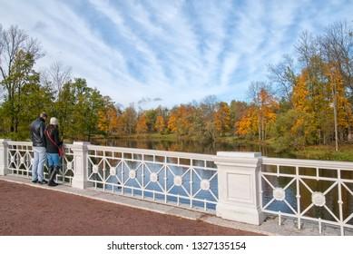 TSARSKOYE SELO, SAINT-PETERSBURG, RUSSIA – OCTOBER 8, 2018: People on The Large Lamsky Bridge near The Lamsky Pond in landscape area of Alexander Park