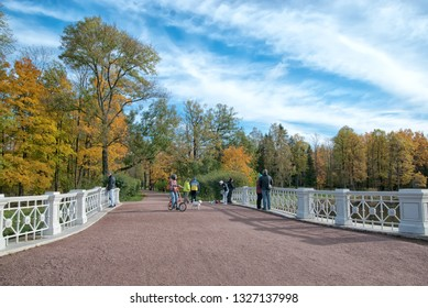 TSARSKOYE SELO, SAINT-PETERSBURG, RUSSIA – OCTOBER 8, 2018: People and dogs on The Large Lamsky Bridge near The Lamsky Pond in landscape area of Alexander Park