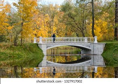 TSARSKOYE SELO, SAINT-PETERSBURG, RUSSIA – OCTOBER 8, 2018: Woman on Third Lamsky Bridge near Lamsky Pond in the landscape area of Alexander Park