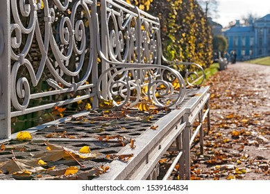 Tsarskoye Selo, Saint-Petersburg, Russia - October 15, 2019: Decorative white bench with autumn yellow leaves in The Catherine Park in front of The Catherine Palace in The State Museum Preserve