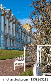 Tsarskoye Selo, Saint-Petersburg, Russia - October 15, 2019: Decorative white benches in The Catherine Park in front of The Catherine Palace and The Church of the Resurrection
