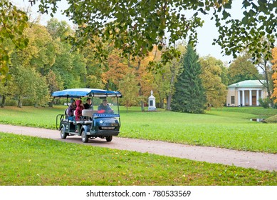 TSARSKOYE SELO, SAINT-PETERSBURG, RUSSIA - OCTOBER 7, 2017: People have excursion in the electric car in The Catherine Park. On the background is The Concert Hall Pavilion