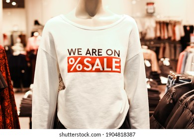 T-shirt with advertising text 'we are on sale' on mannequins in a clothing store. Retail shopping.