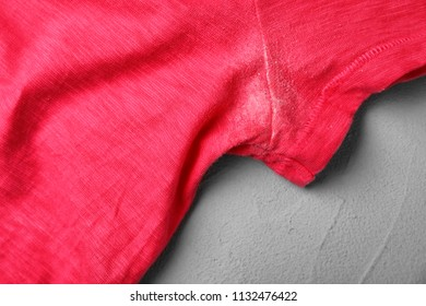 T-shirt with deodorant stain on grey background, closeup
