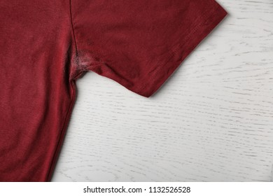 T-shirt with deodorant stain on light background, closeup