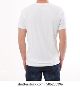 t-shirt design and people concept - close up of young man in blank t-shirt, shirt rear  isolated. Look here. The boy points to the free space. Mock up for design