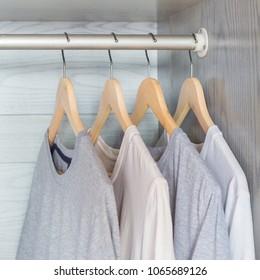 T-shirt hanging on wood hanger on rack in cloth wardrobe