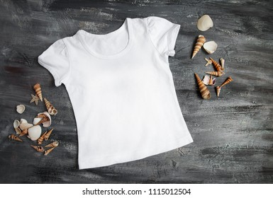T-shirt Mock Up Baby white clothes on Black Wood for design template with sea shells