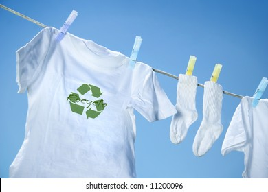 T-shirt with recycle logo drying on clothesline on a summer day