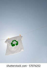 A t-shirt with the recycling symbol hanging on a clothesline