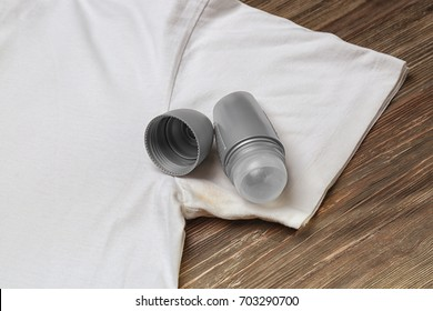 T-shirt with sweat stain and deodorant for man on wooden background