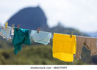 T-shirts and clothes hanging on a clothesline in front of blue sky and the Piedra el Penol with blue cloudy sky inn Guatape near Medellin, Colombia. Defocussed background.