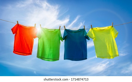 T-shirts hanging on a clothesline in front of blue sky and sun